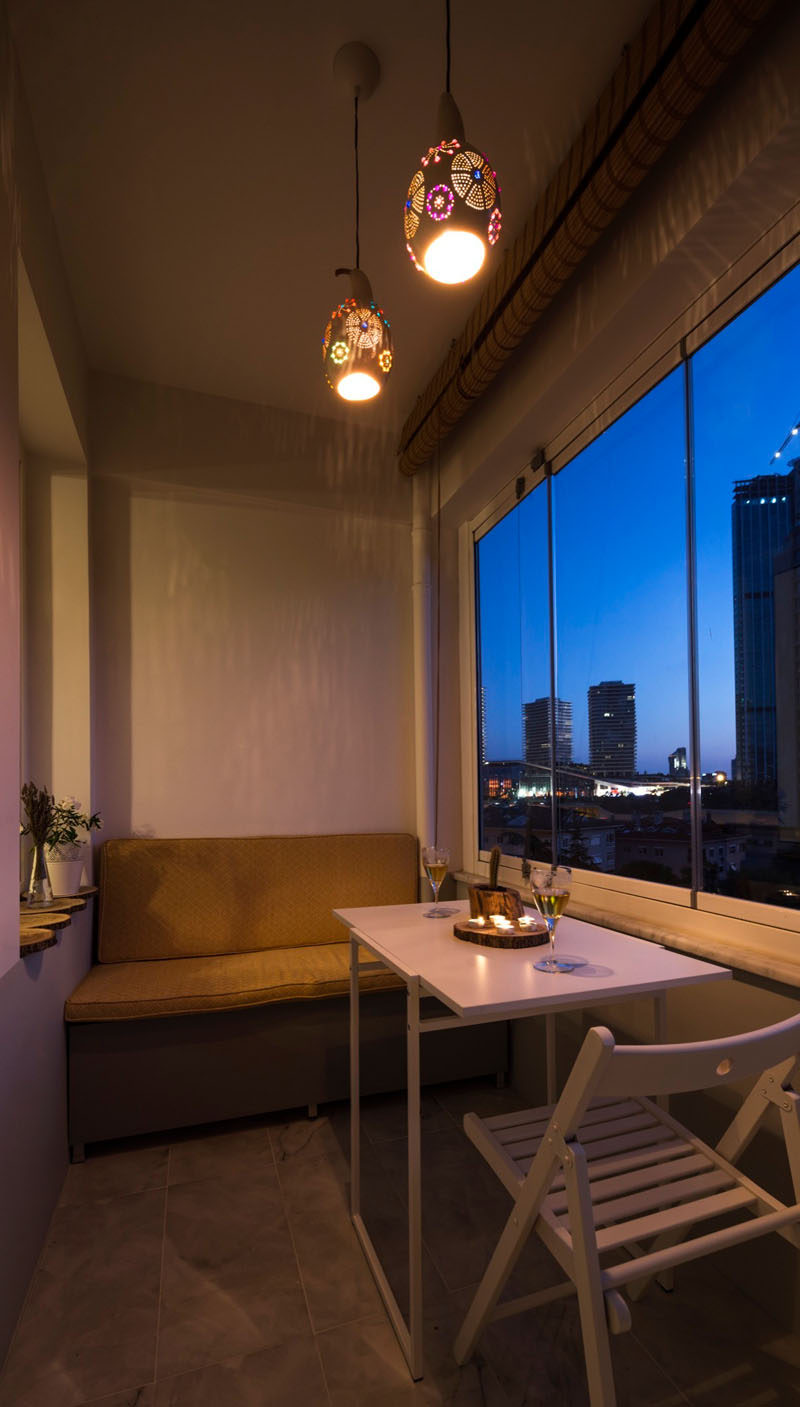 This small enclosed balcony has small built-in banquette and a set of decorative pendant lights help to create a relaxing atmosphere.