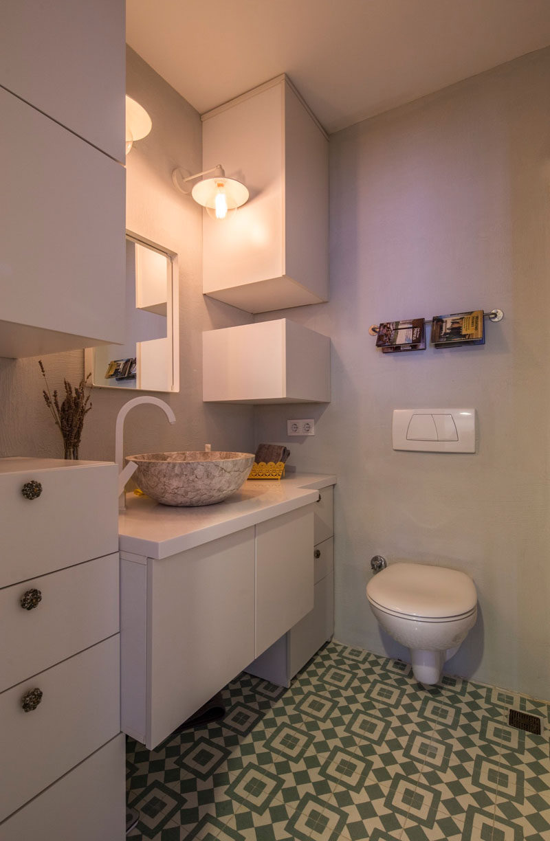 When designing this bathroom, the interior designers used the height of the room to create additional storage that reaches all the way to the ceiling.