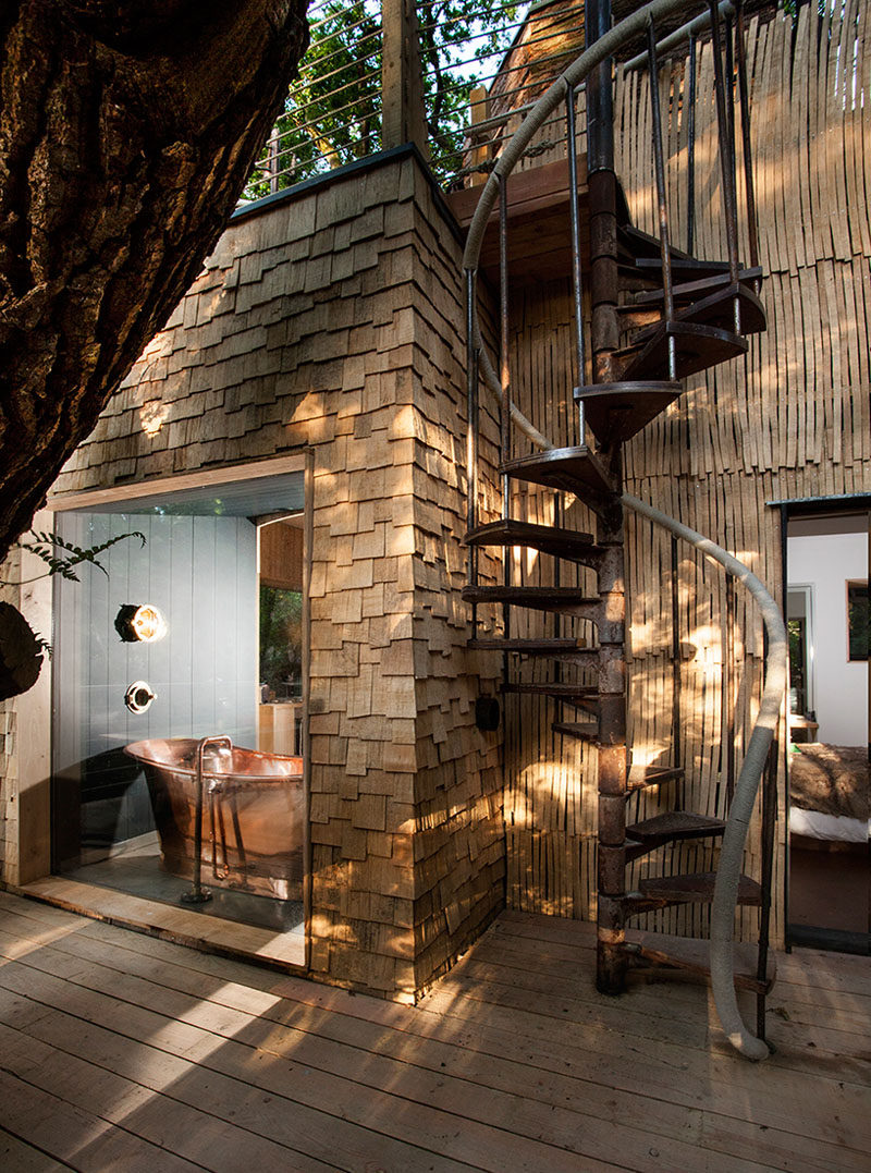 A spiral staircase leads you up to the second storey of this treehouse for adults.