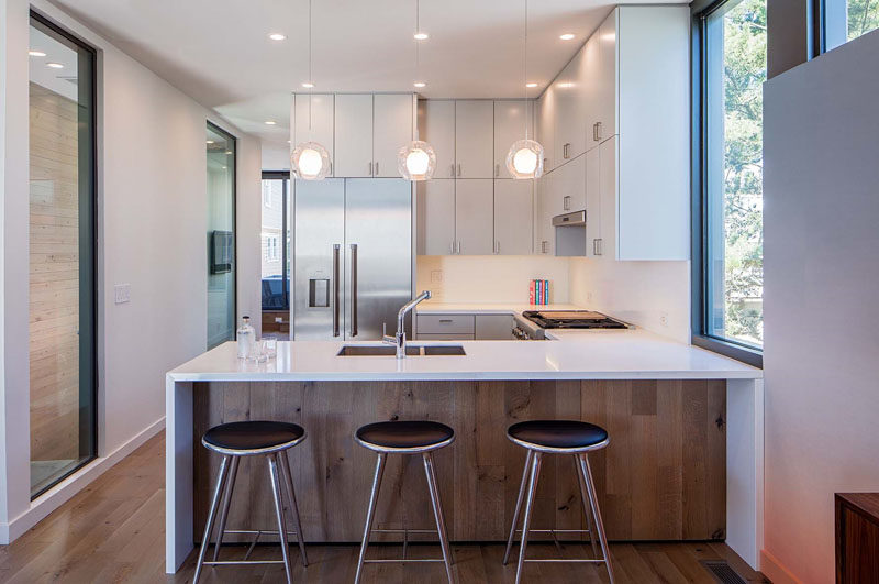 In this kitchen, the cabinets go all the way to the ceiling creating plenty of storage, and part of the countertop overhangs and provides a place for seating.