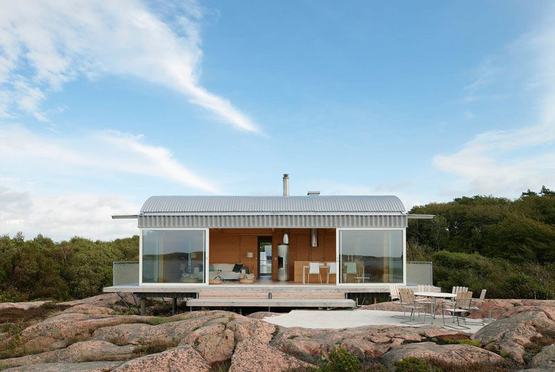 19 Examples Of Modern Scandinavian House Designs | Large glass windows make up the front of this summer house to take advantage of the seaside views.