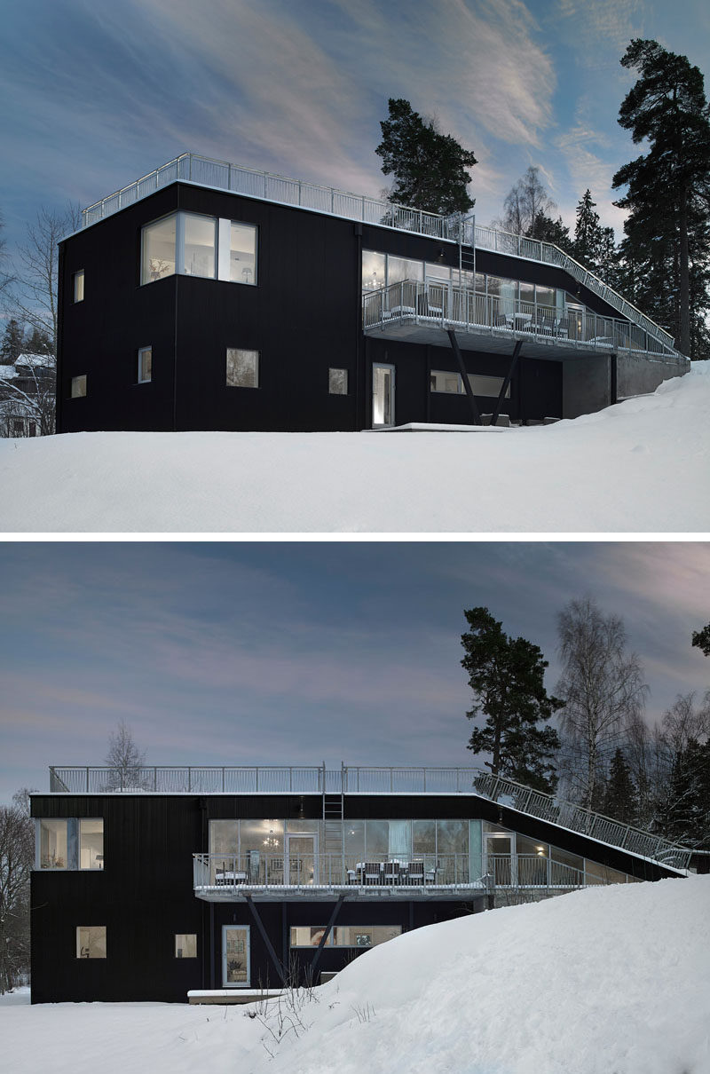 19 Examples Of Modern Scandinavian House Designs | The black metal siding that covers the exterior of this Swedish home makes the house stand out against the snow that covers the ground in the winter, and pop out from the greenery around it in the summer.